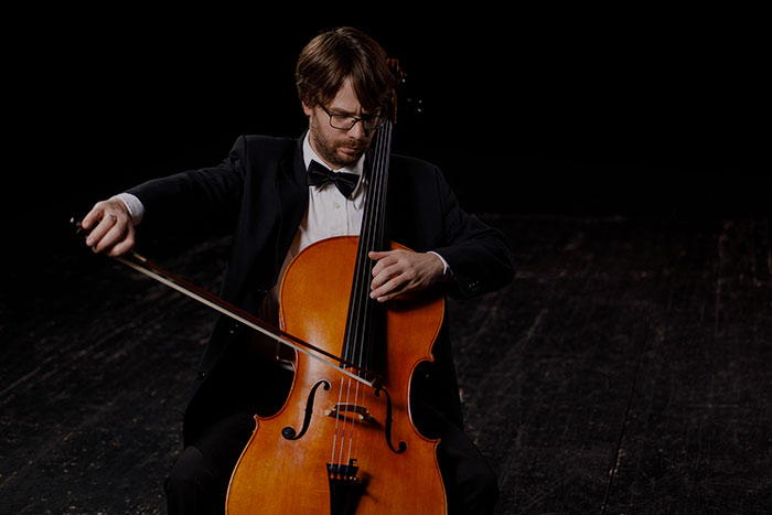 Man playing the cello on stage