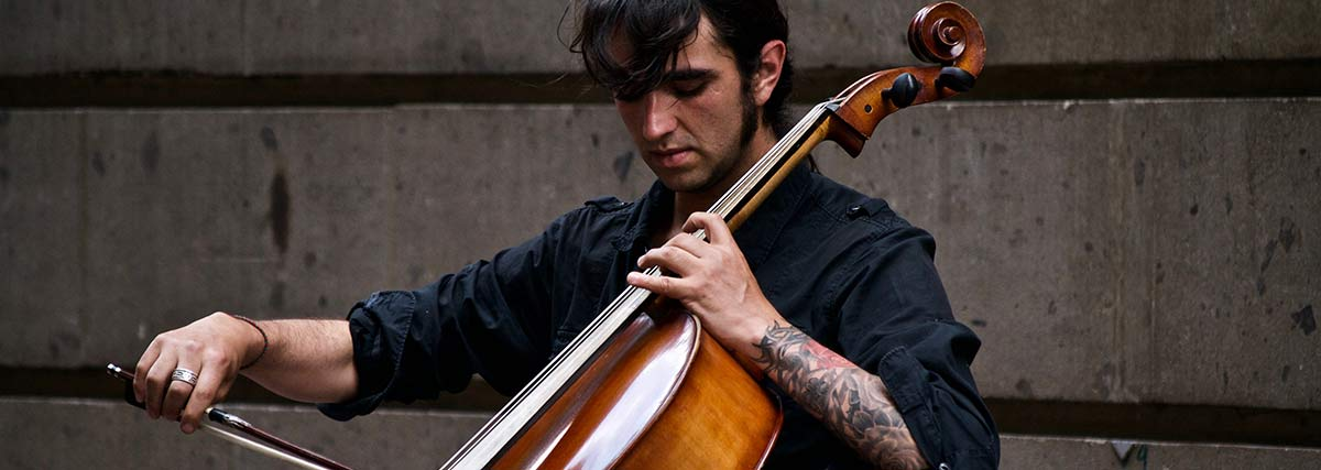 man playing the cello outside the building
