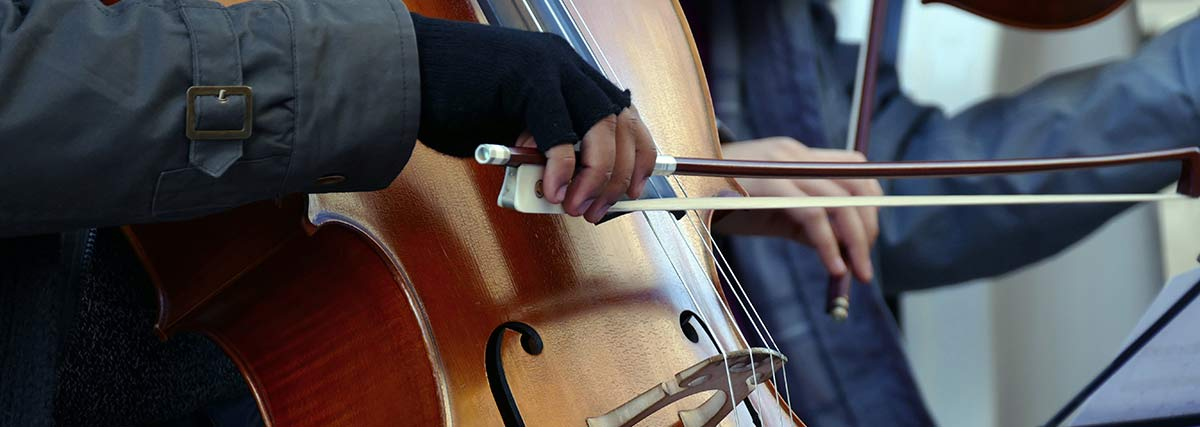man playing cello in cold weather