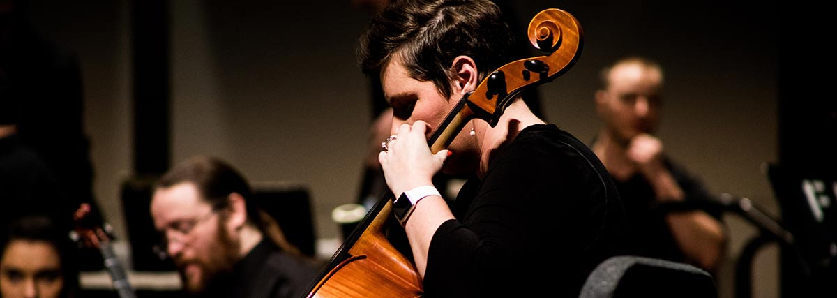 woman playing the cello with an ensemble